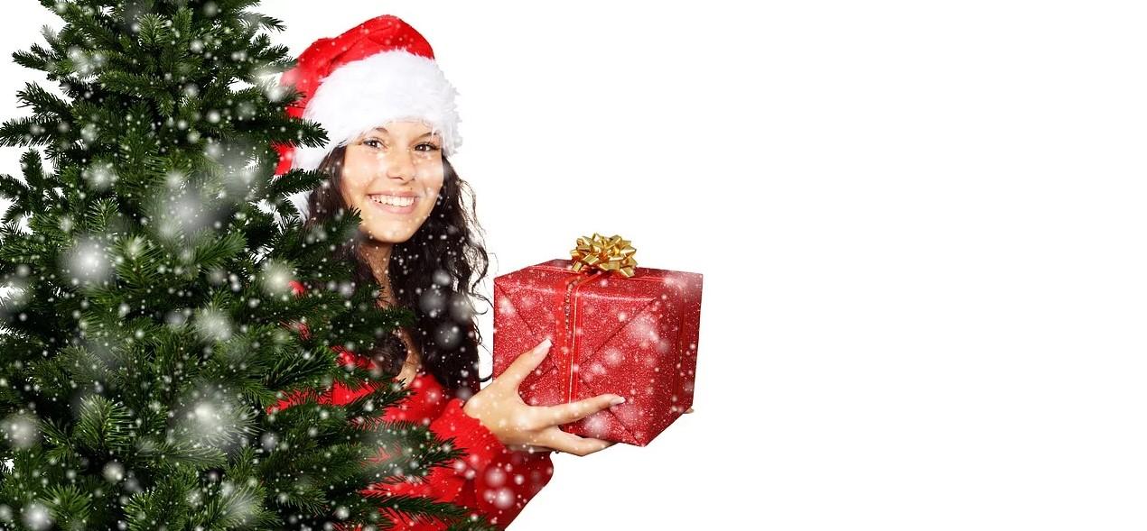 Pige bag juletræ giver gave